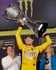 Kyle Busch holds up his trophy in Victory Lane after winning the NASCAR Cup Series auto racing season championship Sunday at Homestead-Miami Speedway in Homestead, Florida.
