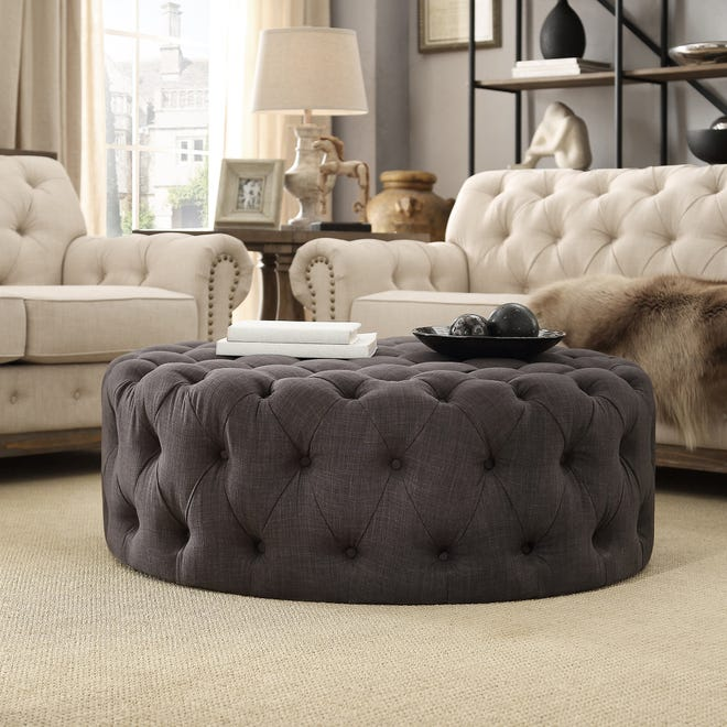 Round elements lend a comforting touch to the home like this tufted ottoman that softens the straight lines of the sofas.
