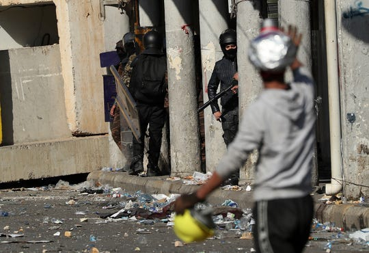 Riot police try to disperse anti-government protesters during clashes with anti-government demonstrators in al-Rashid Street, in Baghdad, Iraq, Sunday, Nov. 17, 2019.