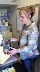 Caroline Fardig mixes chocolate chips into batter in the kitchen at Honey + Moon Kitchen.