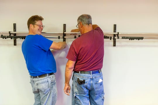 Jacob Messer of Henderson, left, laughs with coworker Bruce Hensley of Niagara while mounting a coat rack at Big Rivers Electric Corporation's first annual Impact Week at the Salvation Army in Henderson, Monday morning.