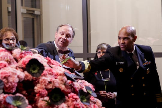 "U.S. Surgeon General Jerome Adams, right, removes a black poppy from the ""Hope Stems"" art exhibit in the Wilmeth Active Learning Center, Monday, Nov. 18, 2019 at Purdue University in West Lafayette. ""Hope Stems"" is a brain-shaped sculpture created out of 9,000 pink carnations and 300 black poppies, the black flowers symbolizing opioid brain damage."