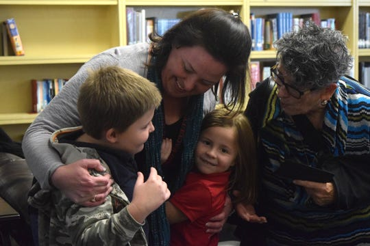Northside High Principal Julia Williams, center,  hugs her children and mother after being surprised with the Lafayette Parish Principal of the Year Award on Nov. 18, 2019.