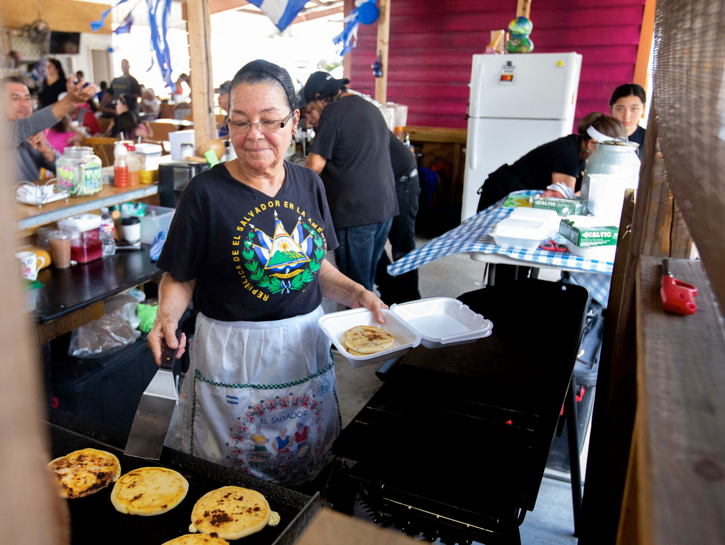Ana Isabel Palencia, 67, prepares pupusas at Pupuseria La Milpa, a family business at the West Bank Flea Market.