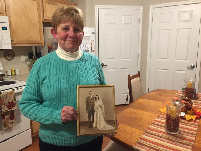 Maureen Borener-Walker holds a wedding photograph of her parents Clarence and Rita at her Oceola Township home, Wednesday, Nov. 13, 2019.