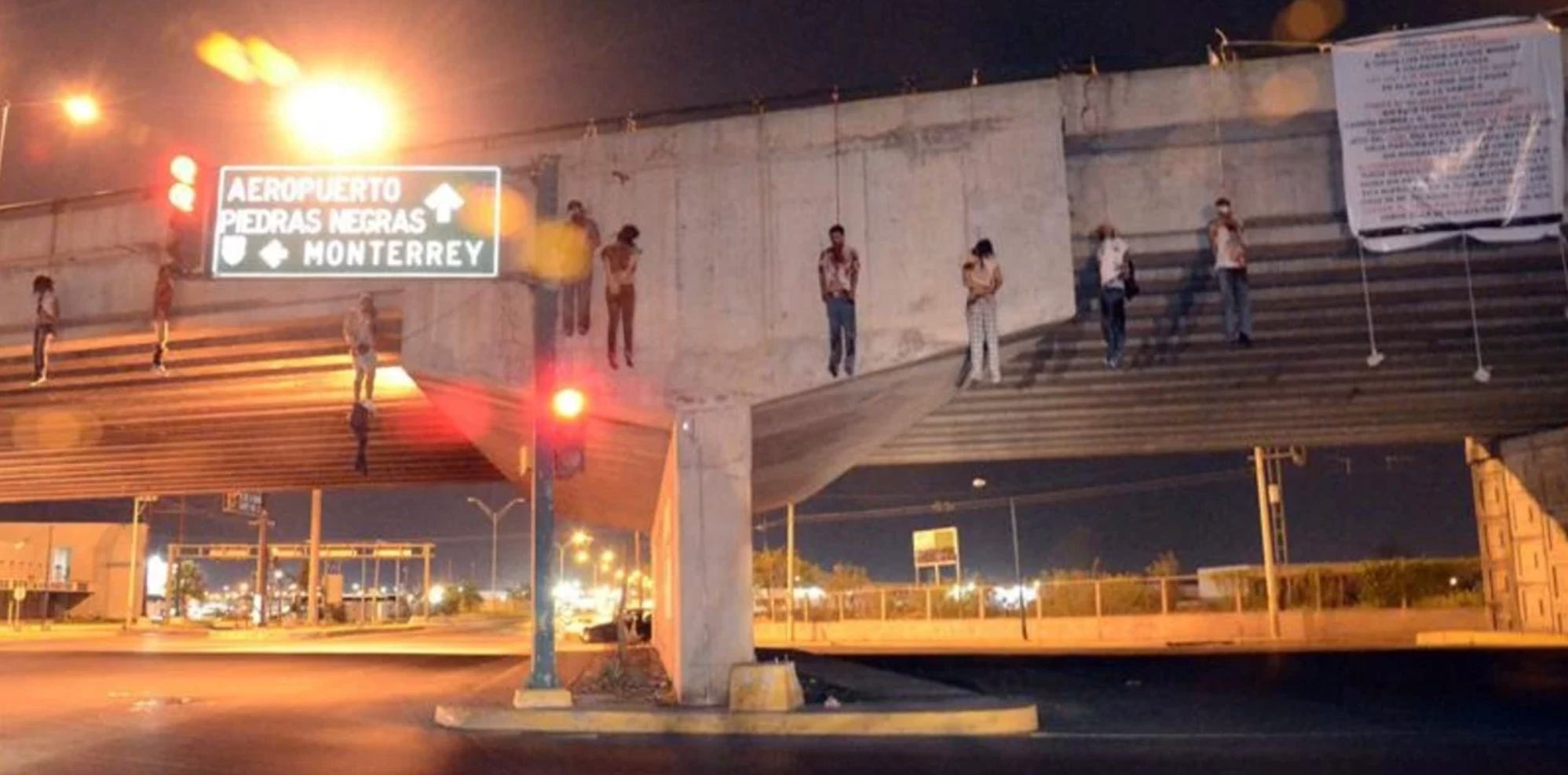 Nine bodies were left hanging from a busy stretch of highway near Nueva Laredo, Mexico. CJNG hung a banner, at right, taking credit.