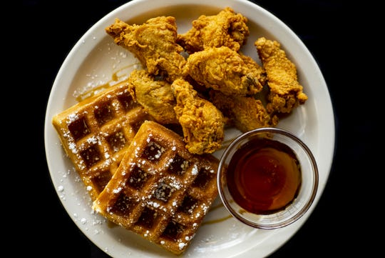 The chicken and waffles at Dasha Barbours Southern Bistro are drizzled with maple syrup and dusted with powdered sugar.