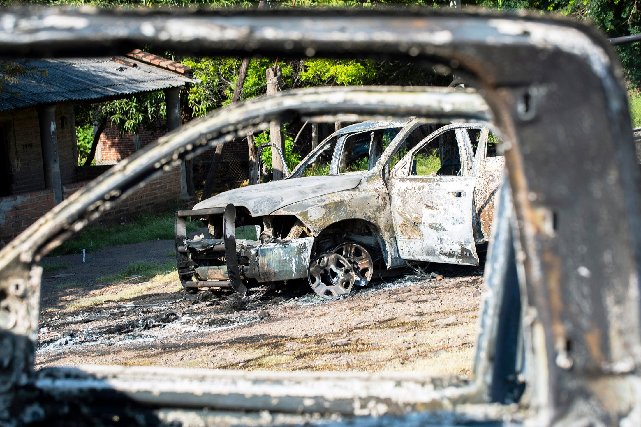 Gunmen opened fire on police, killing 13 officers in an ambush in the community of Aguililla, in the Mexican state of Michoacán, on Oct. 14, 2019. Cartel members also torched at least two patrol cars in the ensuing chaos and left signs with threatening messages.