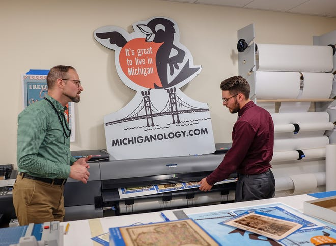 Processing Archivist Peter Richards, left, and Assistant Archivist Jason Schultz print a sheet of puzzle box covers Friday, Nov. 15, 2019. The shop has over 50 puzzle designs and plan to create more.