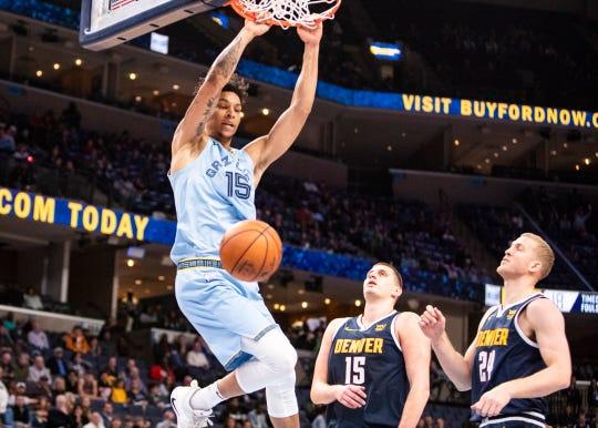Memphis Grizzlies forward Brandon Clarke (15)] dunks the ball against Denver Nuggets center Nikola Jokic (15) and forward Mason Plumlee  (24) at the FedEx Forum on Sunday, Nov. 17, 2019.