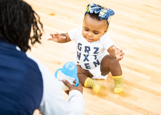 Hazel Collier's parent entices her with a cup of milk during the Memphis Grizzlies Infie 500 baby race at the FedEx Forum on Sunday, Nov. 17, 2019.
