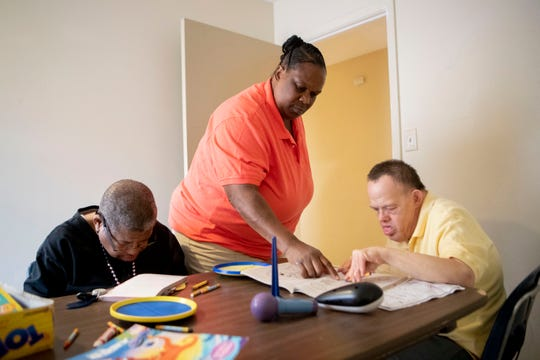 Shelby Residential and Vocational Services home supervisor Wendy Saulsberry works with Michael Scott (left) and Charlie Wayne Allen Wednesday, Oct. 16, 2019, in the activity room at their group home in Memphis.