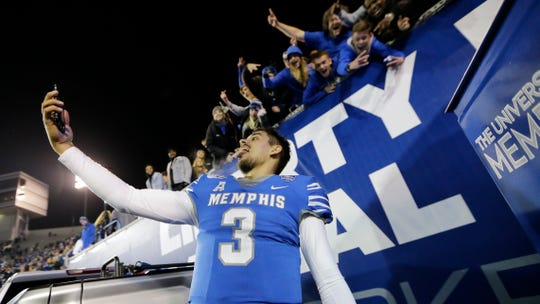 Memphis quarterback Brady White takes a selfie with a fan's phone after the game against SMU on Nov. 2. Memphis won 54-48.