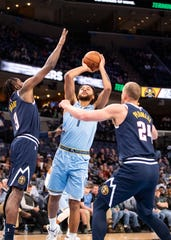 Memphis Grizzlies forward Kyle Anderson (1) shoots the ball over Denver Nuggets  forward Mason Plumlee (24) and forward Jerami Grant (9) during a game at the FedEx Forum on Sunday, Nov. 17, 2019.