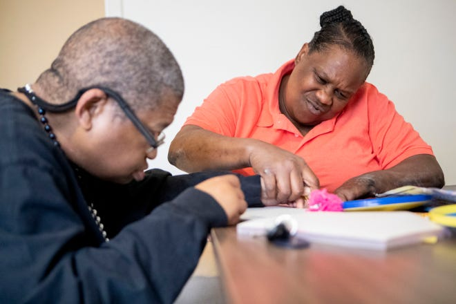 Shelby Residential and Vocational Services home supervisor Wendy Saulsberry helps Michael Scott with a word search Wednesday, Oct. 16, 2019, at his group home in Memphis.