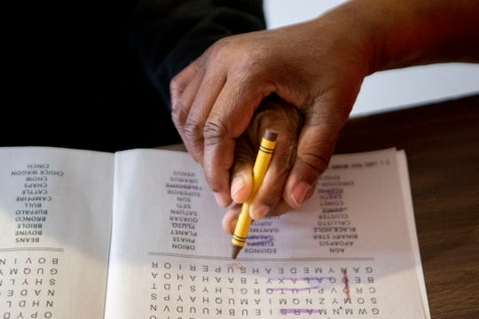 Shelby Residential and Vocational Services home supervisor Wendy Saulsberry helps Michael Scott with a word search Wednesday, Oct. 16, 2019, at their home in Memphis.