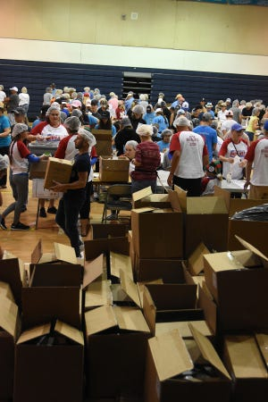 File: Many hands fill many boxes with many meals. A team of over 500 volunteers packed 250,000 meals for hungry families in the Meals of Hope packing event at MICMS, after raising nearly $50,000 for the ingredients.