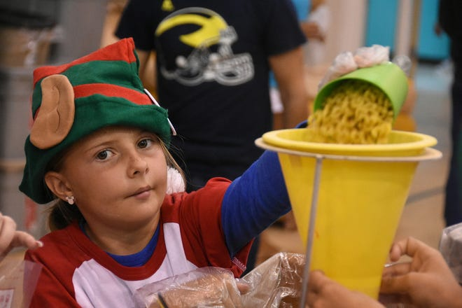 Brighton Subko, 9, fills a meal bag with noodles. A team of over 500 volunteers packed 250,000 meals for hungry families Saturday morning in the Meals of Hope packing event at MICMS, after raising nearly $50,000 for the ingredients.