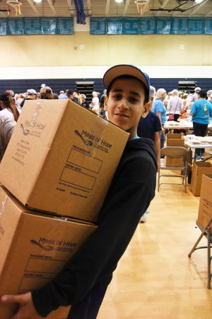 A young volunteer, too busy to give his name, carries cartons of completed meals. A team of over 500 volunteers packed 250,000 meals for hungry families Saturday morning in the Meals of Hope packing event at MICMS, after raising nearly $50,000 for the ingredients.