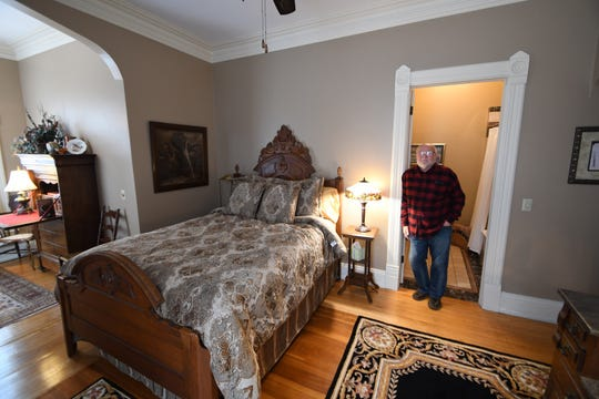 Fargo Mansion Inn owner Tom Boycks stands in the bed and breakfast's Elijah Harvey room.