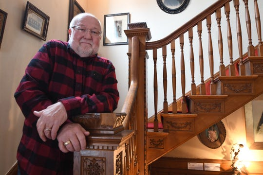 Tom Boycks stands on the stairwell in the Fargo Mansion Inn, which he owns with his partner, Barry Luce.