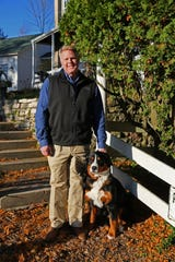 John Baumann, here with his puppy Lainey, bought the house three years ago.