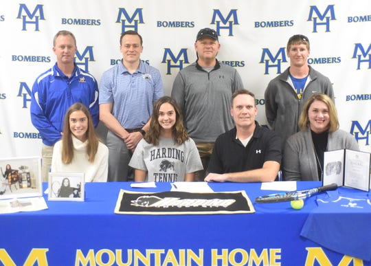 Mountain Home's Emily Heide (front, second from left) signed a National Letter of Intent on Monday to play tennis at Harding University. Pictured with Heide are: (front row) her sister Macie Heide, her father Brian Heide, her mother Misti Heide; (back row) MHHS athletics director Mitch Huskey, Harding  admissions counselor Blake Matty, MHHS tennis assistant Dirk Waldrop, and MHHS head tennis coach Calvin Henry.