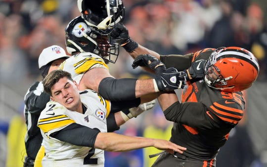 Browns defensive end Myles Garrett (95) hits Steelers quarterback Mason Rudolph (2) with a helmet during Thursday's game.