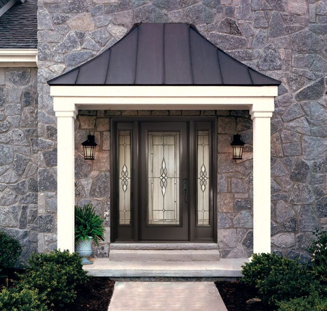 This simple, yet elegant front entry door from Taylor Door in Paterson features decorative glass and side panels, enhancing the curb appeal of this home.