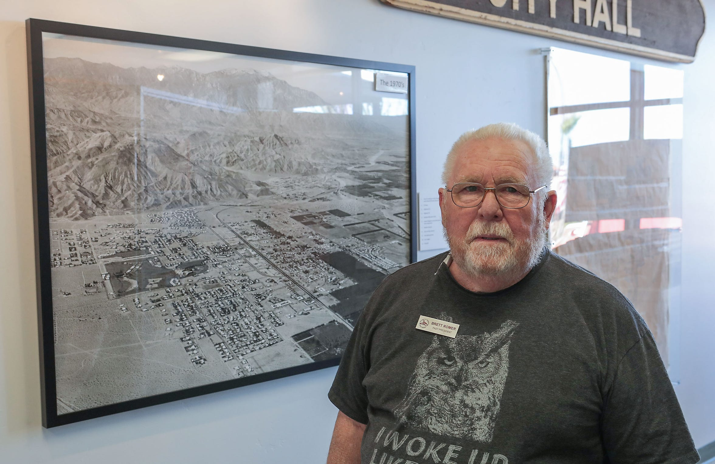Brett Romer of the Historical Society of Palm Desert stands near an old aerial photograph of Palm Desert on Nov. 8, 2019. Romer moved to Palm Desert in 1964 to take a teaching job at College of the Desert, which had just opened to students two years before.