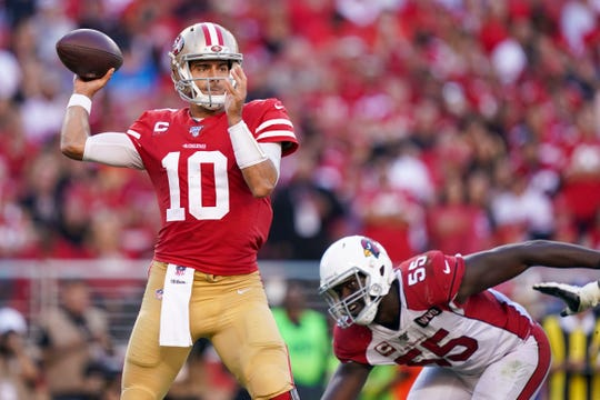 Jimmy Garoppolo of the 49ers looks to pass as Chandler Jones pursues him during the third quarter of a game Nov. 17 at Levi's Stadium.