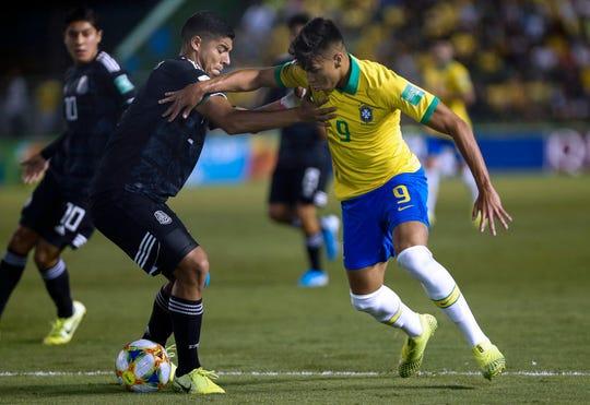 Victor Guzman (izq.) busca frenar el embate del jugador brasileño.