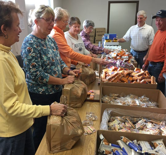 Volunteers from Eastminster Presbyterian Church assemble backpacks of food to be distributed to students from low income families.
