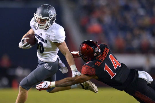 Nevada Wolf Pack wide receiver Ben Putman (10) is defended by San Diego State Aztecs safety Tariq Thompson (14) during the third quarter at SDCCU Stadium.