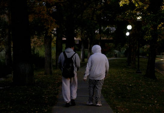 14-year-old Frankie, right, walks in the early morning to school with his father, Franklin, on Oct. 11, 2019.