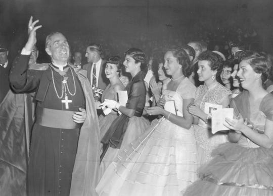Bishop Fulton waves to people in the upper tiers of the Rochester War Memorial. Sheen was Bishop of the Rochester diocese from 1966 to 1969.
