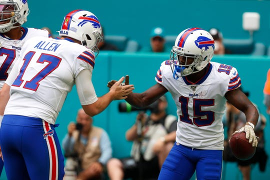 Buffalo Bills quarterback Josh Allen (17) congratulates wide receiver John Brown (15) after Brown scored a touchdown, during the first half of Sunday's game at Miami.