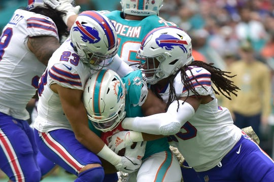 Buffalo Bills defenders Micah Hyde, left, and Tremaine Edmunds  tackle Kalen Ballage of the Miami Dolphins during the first quarter at Hard Rock Stadium on November 17, 2019 in Miami, Florida.