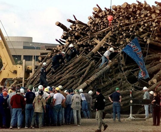 Texas A&M students and rescue workers gather at the base of the collapsed bonfire stack as the search continues for victims Thursday, Nov. 18, 1999, in College Station, Texas. The stacks' center pole, shown in two pieces, one carrying a Corps of Cadets squadron flag, and the second just above, apparently snapped and the stack collapsed. Ten students were killed along with one student graduate.