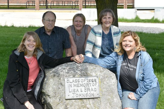Family and friends of Lisa and Brad Johnson pose in front of the memorial tree honoring them. From left to right: Amy Bermke, Brian Johnson, Carrie Johnson, Ellynne Johnson and Gail Wilke.