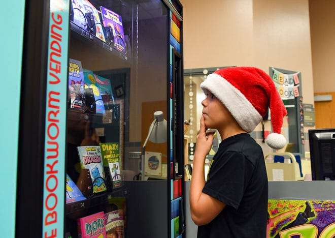 Third-grader Cooper Roettger steps up to Inchy, the Bookworm Vending Machine, to select a book on Monday morning, Nov. 18, at John Harris Elementary.