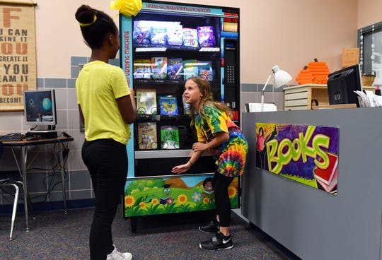 "Fourth-grader Lainey Rogers, right, talks with fifth grader Yididia Demilie as she pulls her book of choice from the slot on Inchy, the ""bookworm vending machine,"" on Monday morning, Nov. 18, at John Harris Elementary."