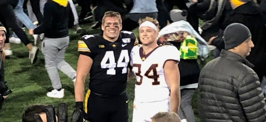 Washington graduates Seth Benson (Iowa) and Brock Walker (Minnesota) pose for a photo following the Gophers vs. Hawkeyes game.