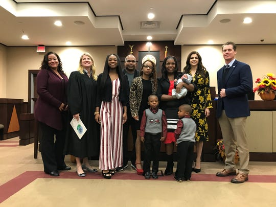 """Olivia Thoomas (third from right) stands with her family and First Lady Casey DeSantis (second from right) to celebrate adopting toddlers Timothy and Christian Monday morning, Nov. 18, 2019. Circuit Judge Angela Dempsey (second from left) holds a copy of """"The Rainbow Fish."""""""