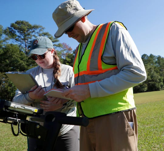 Archeological technicians Haley Messer and Andrew McFeaters review their notes as they search for potential unmarked graves located at the Capital City Country Club golf course on Monday, Nov. 18, 2019.