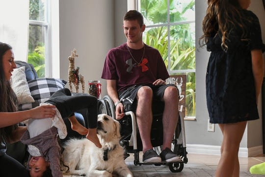 "Chris Norton (center) spends time with his family (from left) his wife Emily, daughters Ariana, 3, Isabella, 6, along with their dog Ivory, as they spend the afternoon playing in their living room on Wednesday, Nov 13, 2019, in Wellington. ""In the wheelchair, you kind of take a little different role. I try to stay as involved, be there and include myself, as much as I can,"" Chris Norton said. ""The kids, they just have fun no matter what. I'm always trying to find ways to interact, and play. I had a dad that did that with me all the time so I try to replicate that the best I can with my new circumstances."""