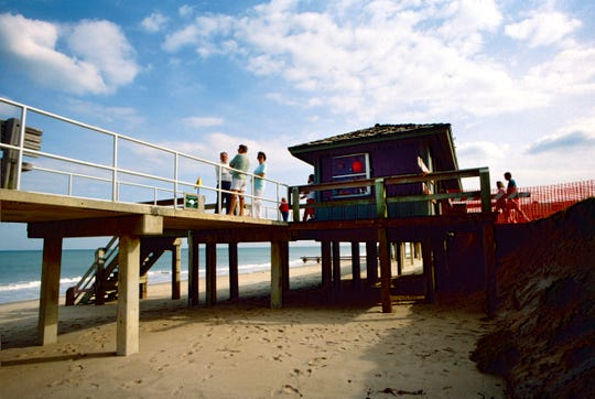 Decades of storms and punishing waves erode the sand around the lifeguard shack at Humiston Beach. This aftermath of a storm in 1993 took all the sand from beneath the guard house, erided the parking lot and closed all of the boardwalks but one near the lifeguard stand.