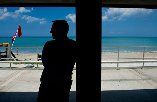 Erik Toomsoo, a lifeguard with the City of Vero Beach, looks out over the ocean at Humiston Park from underneath the guard shack after a 2012 shark bite just north of the beach. Toomsoo is one of three lifeguards credited with helping save the life of Karin Ulrike Stei, who was bitten in the upper thigh while swimming in front of the Driftwood Resort.