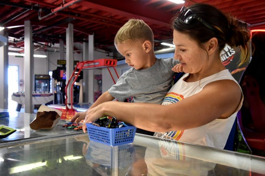 Mayan Flynn, age 2, picks out a car from the prize counter at Village Carousel at Ventura Harbor Village on Monday with the help of his mom, Anna. The Flynns visit the arcade about once or twice per month to play games and win car prizes.