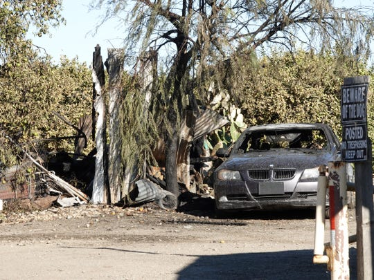 A burned-out car, at right, sits next to wreckage from an intense trailer fire early Sunday as seen from Willard Road east of Santa Paula. A teenager was found dead in the trailer.